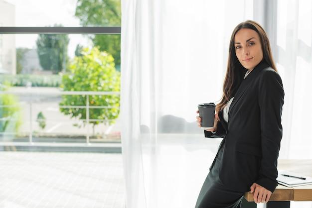 Junge geschäftsfrau, die am rand des hölzernen schreibtisches hält wegwerfkaffeetasse nahe dem fenster sitzt