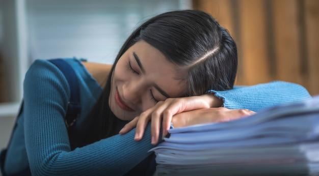 Junge geschäftsfrau, die am schreibtisch tisch schläft, versuchte attrative frau mit stapel von papieren.