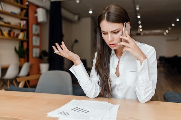 Junge geschäftsfrau, die am telefon bespricht geschäft im büro spricht