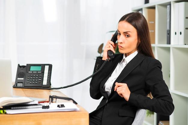 Junge geschäftsfrau, die am telefon sitzt nahe dem schreibtisch spricht