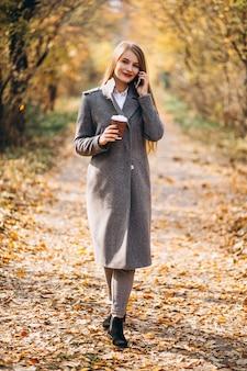 Junge geschäftsfrau, die am telefon spricht und kaffee trinkt