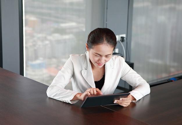 Junge geschäftsfrau, die am tisch auf arbeitsplatz im büro mit dem spielen der tablette sitzt
