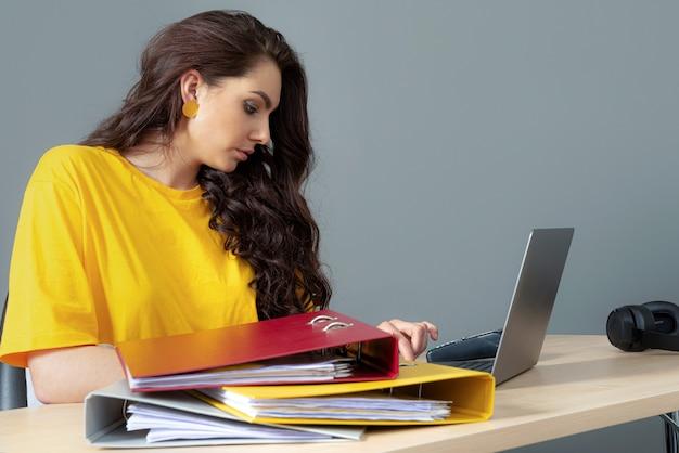 Junge geschäftsfrau, die am tisch sitzt und mit dokumenten und laptop arbeitet, lokalisiert auf grauer oberfläche