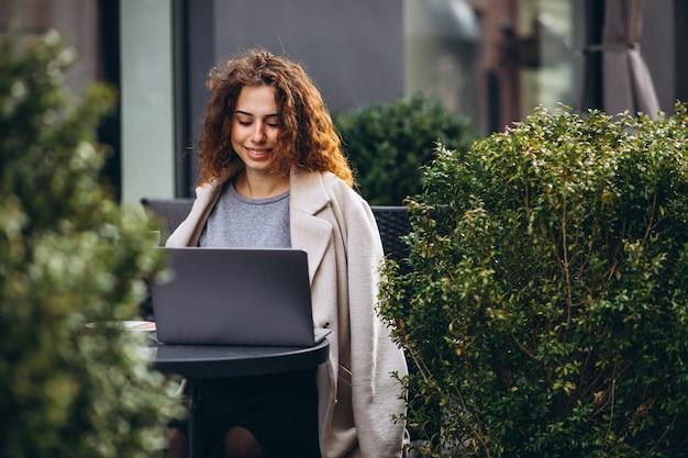 Junge geschäftsfrau, die an einem computer außerhalb des cafés arbeitet