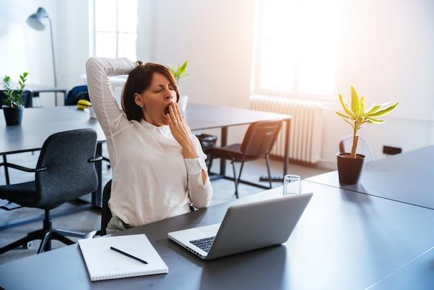 Junge geschäftsfrau, die an einem modernen schreibtisch vor laptop gähnt
