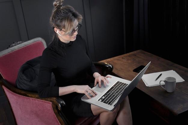 Junge geschäftsfrau, die an ihrem laptop im büro arbeitet