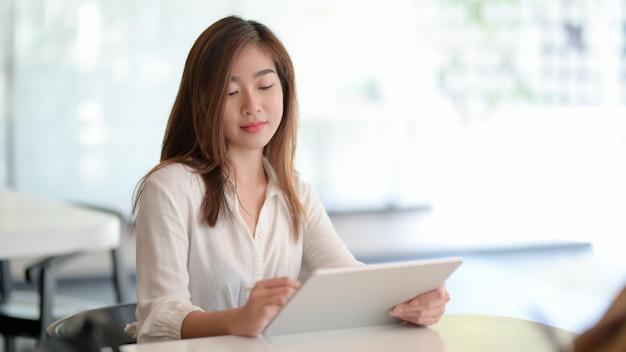 Junge geschäftsfrau, die an ihrem projekt bei der anwendung der digitalen tablette arbeitet