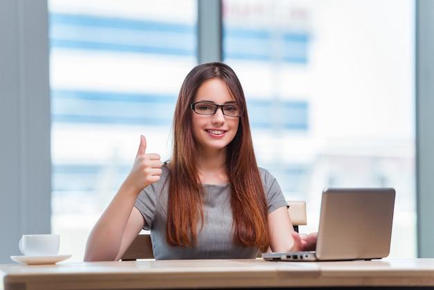 Junge geschäftsfrau, die an laptop arbeitet