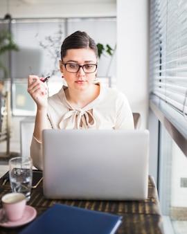 Junge geschäftsfrau, die an laptop in der kaffeestube arbeitet