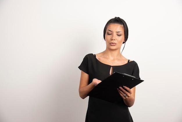 Junge geschäftsfrau, die anmerkungen über weiße wand liest.