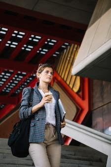 Junge geschäftsfrau, die auf das treppenhaus hält digitalen tabletten- und mitnehmerkaffee geht