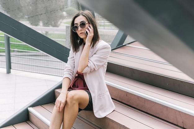 Junge geschäftsfrau, die auf dem treppenhaus spricht auf smartphone sitzt