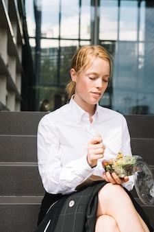 Junge geschäftsfrau, die auf dem treppenhaus zu mittag isst sitzt