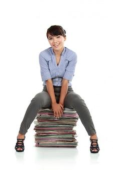 Junge geschäftsfrau, die auf dokumentpapieren sitzt