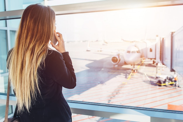 Junge geschäftsfrau, die auf handy spricht und auf ihren flug wartet, der flugzeuge durch das fenster betrachtet, das in abflugzone am flughafen steht