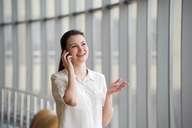 Junge geschäftsfrau, die auf handy spricht, während sie durch fenster im büro steht. schönes junges weibliches modell im büro.