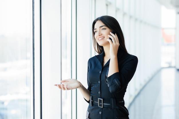 Junge geschäftsfrau, die auf handy spricht, während sie durch fenster im büro steht. schönes junges weibliches modell im hellen büro.