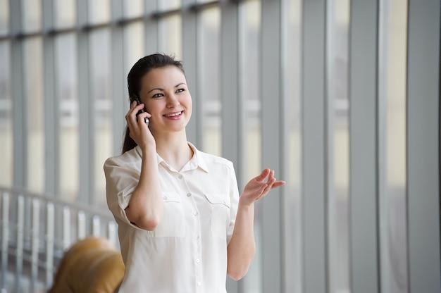 Junge geschäftsfrau, die auf handy spricht, während sie durch fenster im büro steht. schönes junges weibliches modell in einem hellen büro.