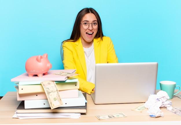 Junge geschäftsfrau, die auf ihrem schreibtisch sitzt und mit einem laptop arbeitet
