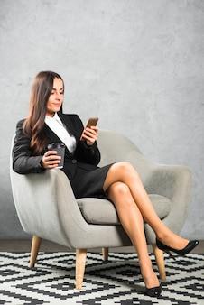 Junge geschäftsfrau, die auf lehnsessel mit den gekreuzten beinen betrachtet mobiltelefon sitzt
