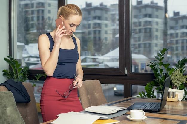 Junge geschäftsfrau, die auf smartphone im büro steht und spricht.