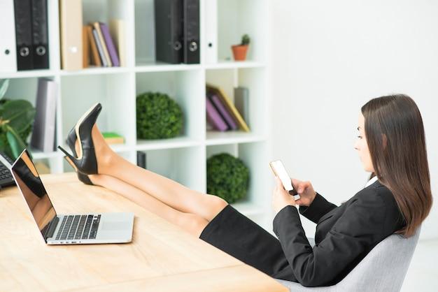 Junge geschäftsfrau, die auf stuhl mit den gekreuzten beinen auf schreibtisch unter verwendung des smartphone sitzt