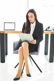 Junge geschäftsfrau, die auf stuhl mit den gekreuzten beinen schreibt auf klemmbrett sitzt