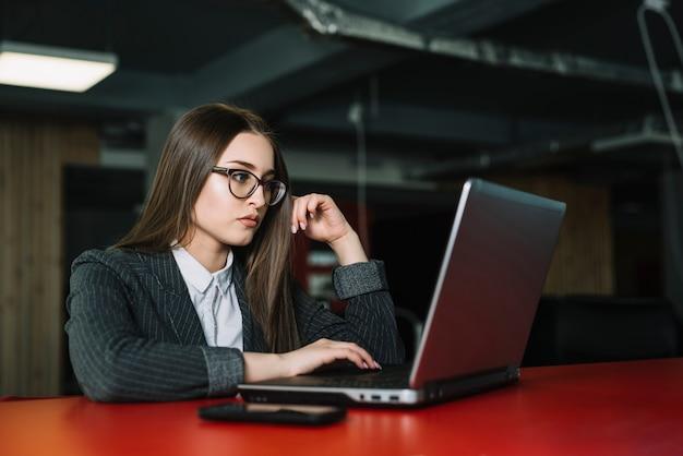 Junge geschäftsfrau, die bei tisch laptop verwendet