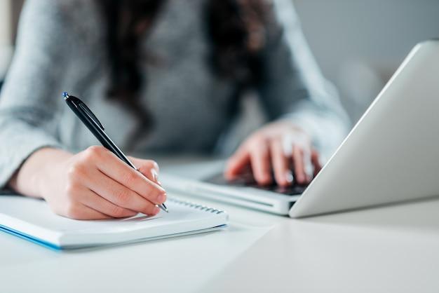 Junge geschäftsfrau, die bei tisch mit laptop sitzt und kenntnisse im notizbuch nimmt.