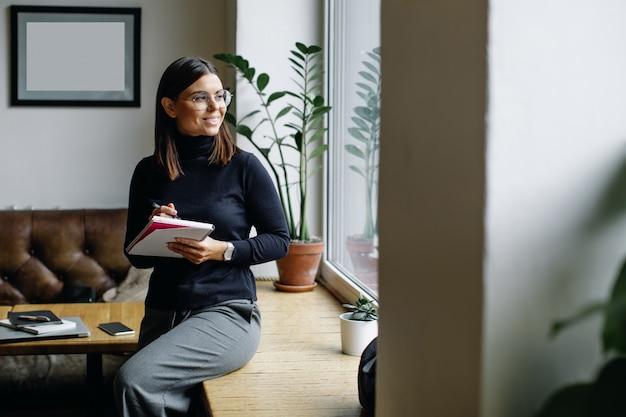Junge geschäftsfrau, die bei tisch sitzt und kenntnisse im notizbuch nimmt.