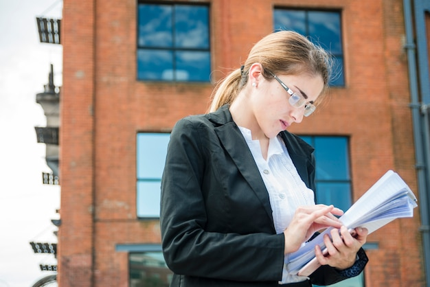 Junge geschäftsfrau, die die dokumentenpapierstellung außerhalb des bürogebäudes liest