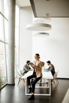 Junge geschäftsfrau, die digitales tablett vor ihrem team in einem modernen büro verwendet