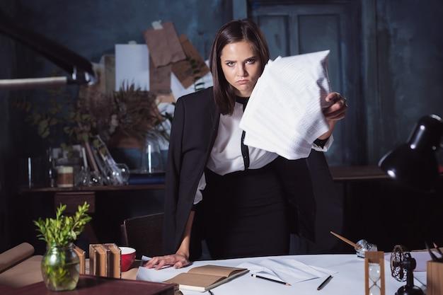Junge geschäftsfrau, die dokumente wirft. enttäuscht und verärgert über erfolgloses projekt.