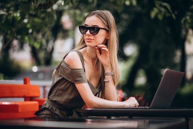 Junge geschäftsfrau, die draußen an laptop in einem café arbeitet