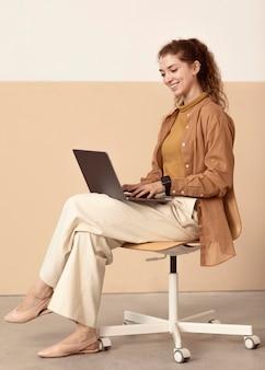 Junge geschäftsfrau, die drinnen vom laptop arbeitet