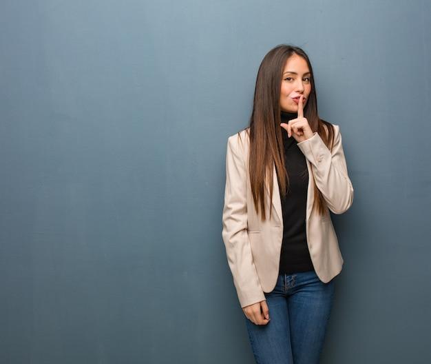 Junge geschäftsfrau, die ein geheimnis hält oder um ruhe bittet