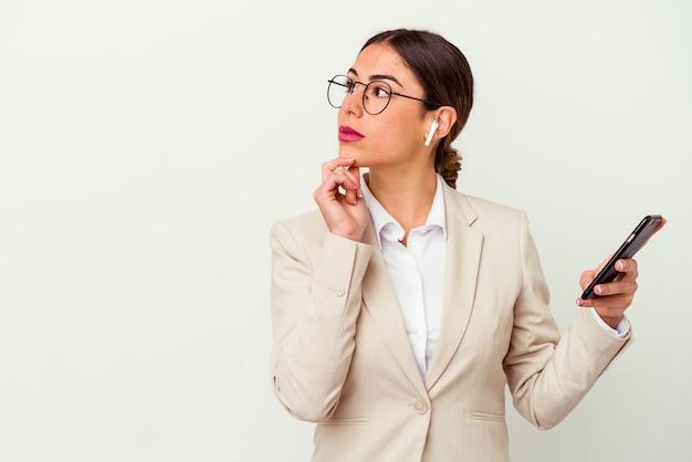 Junge geschäftsfrau, die ein mobiltelefon lokalisiert auf weiß hält, das seitlich mit zweifelhaftem und skeptischem ausdruck schaut.