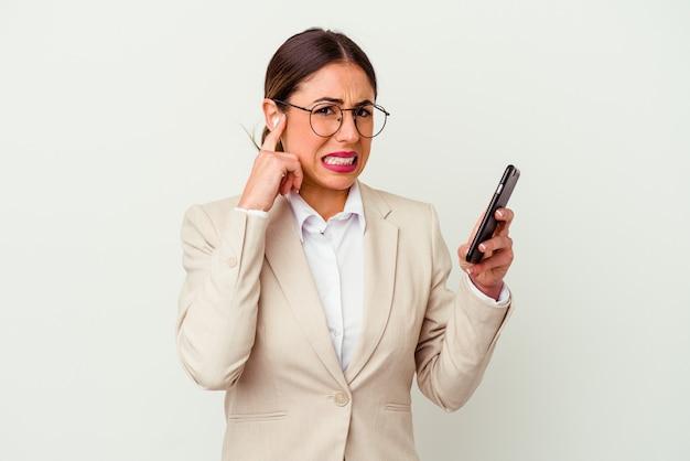 Junge geschäftsfrau, die ein mobiltelefon lokalisiert auf weißer wand hält, die ohren mit händen bedeckt.