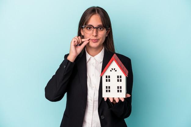 Junge geschäftsfrau, die ein spielzeughaus lokalisiert auf blauem hintergrund mit den fingern auf den lippen hält, die ein geheimnis halten.