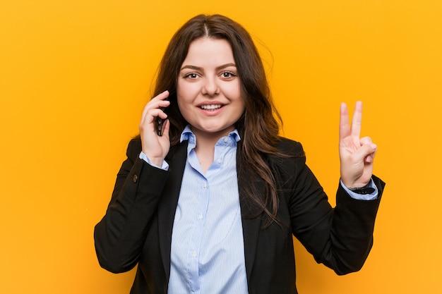Junge geschäftsfrau, die ein telefon hält, das nummer zwei mit den fingern zeigt