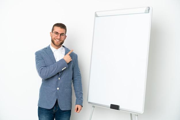 Junge geschäftsfrau, die eine präsentation auf weißer tafel lokalisiert auf weißem hintergrund zeigt, der zur seite zeigt, um ein produkt zu präsentieren