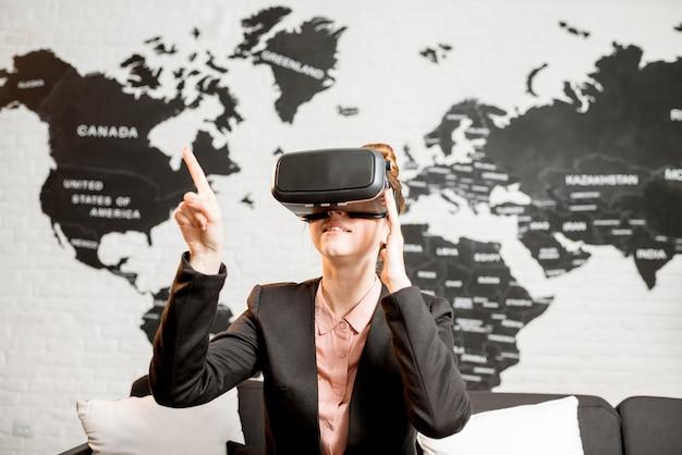 Junge geschäftsfrau, die eine virtual-reality-brille versucht, die drinnen mit weltkarte im hintergrund sitzt