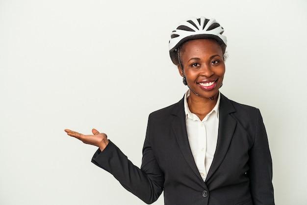 Junge geschäftsfrau, die einen fahrradhelm trägt, der auf weißem hintergrund lokalisiert wird, der einen kopienraum auf einer handfläche zeigt und eine andere hand auf taille hält.