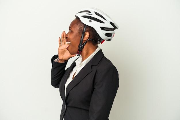Junge geschäftsfrau, die einen fahrradhelm trägt, isoliert auf weißem hintergrund, schreit und hält die handfläche in der nähe des geöffneten mundes.