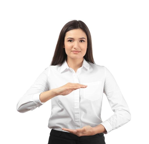 Junge geschäftsfrau, die etwas auf weiß hält