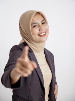 Junge geschäftsfrau, die fröhlich auf die isolierte weiße wand der kamera zeigt