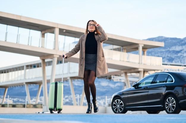 Junge geschäftsfrau, die gegen schwarzes luxusauto geht