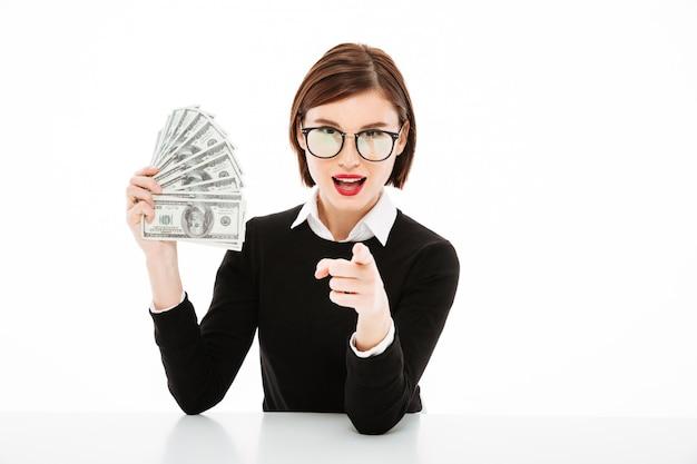 Junge geschäftsfrau, die geld zeigt und mit dem finger zeigt