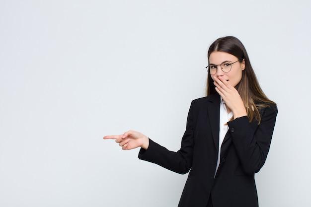 Junge geschäftsfrau, die glücklich, schockiert und überrascht fühlt, mund mit der hand bedeckt und auf seitlichen kopierraum über weißer wand zeigt