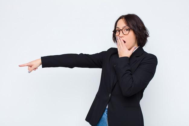 Junge geschäftsfrau, die glücklich, schockiert und überrascht fühlt, mund mit hand bedeckt und auf seitlichen kopierraum gegen weiße wand zeigt